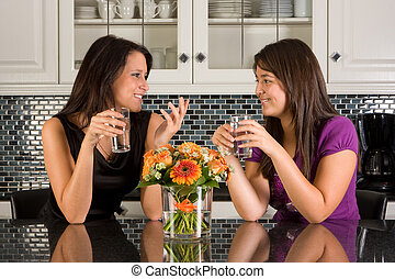 Talking in the kitchen - Two friends drinking water in a...