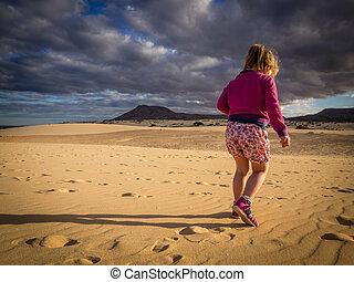 Little girl walking on the sand dunes