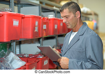 Man in warehouse using tablet