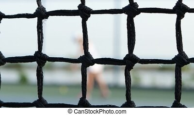 Girl tennis player expecting the tennis ball on court, net...
