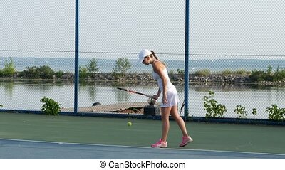 Women playing tennis. Player serving tennis ball with tennis...