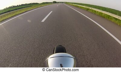Motorcycle riding on asphalt, dirt road. Close up