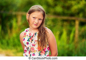Outdoor portrait of a cute little girl of 8 years