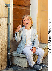 Outdoor fashion portrait of a cute little boy of 5 years...