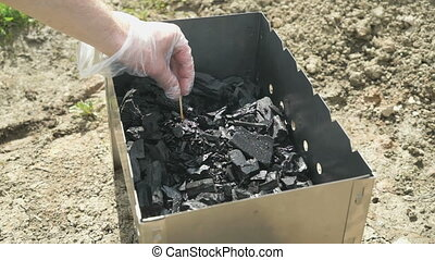 Hand with a burning match ignites the charcoal soaked with...