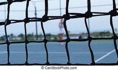 Tennis net and girl tennis player in the background