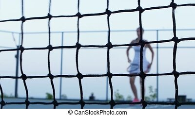 Tennis ball hits net. Tennis player in the background -...