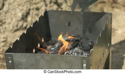 Charcoal put in the brazier with a blazing fire outdoors