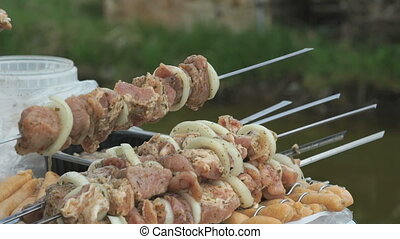 Humans hand strung pieces of raw meat on a skewer outdoors