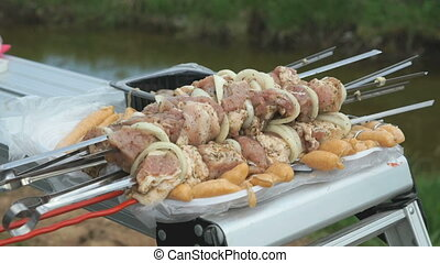Man takes the skewers with fresh meat for roasting over hot...