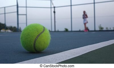 Tennis court with tennis balls and player - Tennis ball on...
