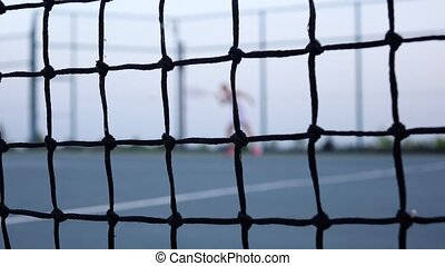 Training a tennis player Net in front - Female tennis player...
