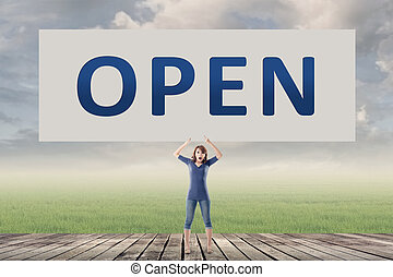 Open sign - Open, words on blank board hold by a young girl...