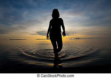 Silhouette of woman walking in shallow water during sunrise