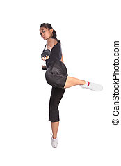 Female fitness trainer in fighting pose with one leg in air in side kick position.