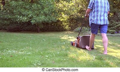Man working in garden cutting grass with lawn mower. 4K -...