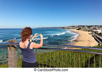 Bar Beach - Newcastle Australia - A women takes a photo with...