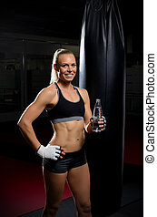 Kickboxer woman with water bottle at gym
