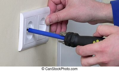 Electrician hands install electrical wall sockets -...