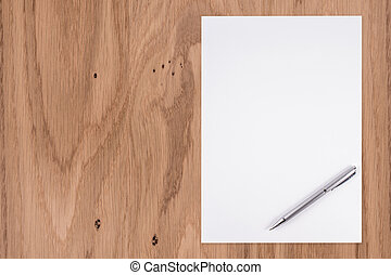 Blank white paper with pen on a wooden desk.