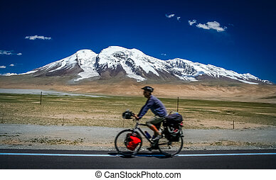 Cycling in front of Muztagh Ata - Single male cyclist on the...