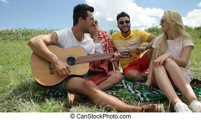 Young people listening guy playing guitar group friends summer day sitting green grass