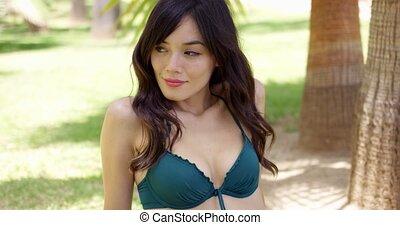 Grinning woman in bikini top near palm tree - Grinning woman...