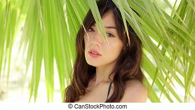 Shy young woman in shade of palm leaves - Single gorgeous...