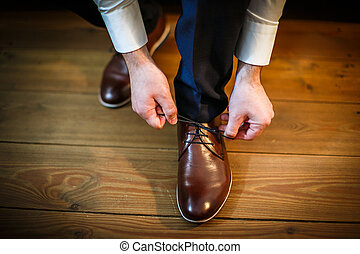 Handsome groom on his wedding day - tying a shoe lace
