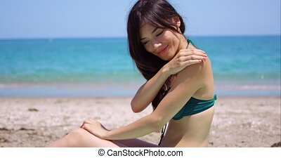 Smiling woman applying suntan lotion on a beach - Smiling...