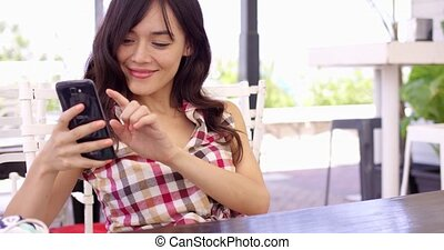 Young woman relaxing on a patio with a mobile - Young woman...