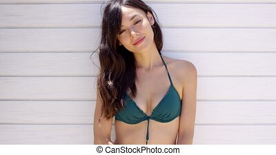 Woman wearing bikini top stretches in the sun while taking a...