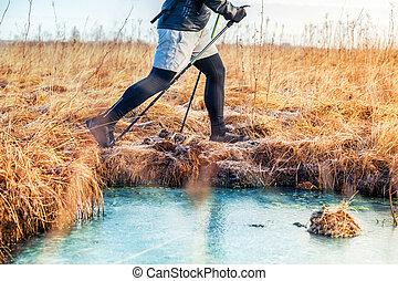 Men trail walking near the frozen river