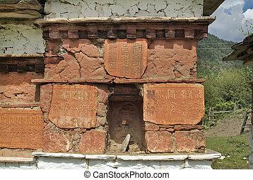 Bhutan, Paro, - Bhutan, Mani wall with symbols in Paro...