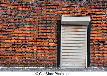 Red brick wall and iron closed door - Red brick wall with...