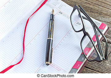 Fountain pen and notebook planner with eyeglasses