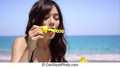 Young woman blowing soapy iridescent bubbles as she relaxes...