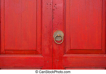 Brass door handle and knocker in chinese style on a red wooden door