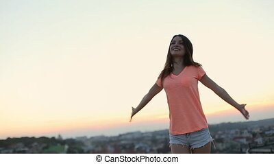 Young woman stands on the roof with great cityscape view and takes in the surrounding beauty, she raises her arms and jumps up and down