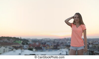 Girl in orange t-shirt and blue shorts with dark flying hair...
