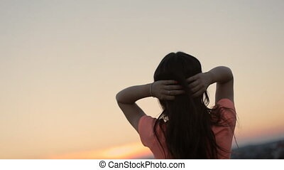 Free happy brunette woman raising arms watching the sun and touching her long hair in the background at sunset