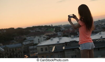 Charming tourist taking photograph of the urban city at sunset, view from roof