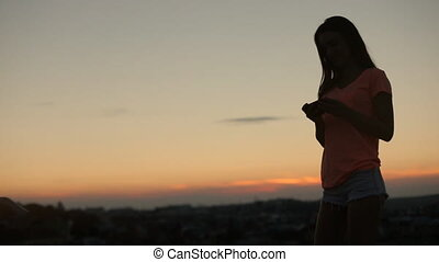 Side shot of young woman using cell phone over city skyline at sunset