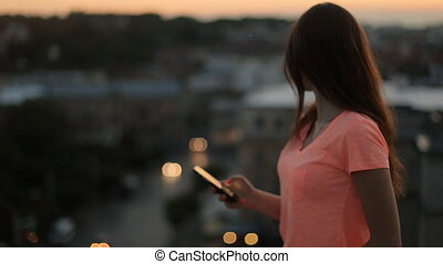 Young woman in orange t-shirt using smartphone on terrace...
