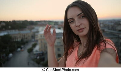 Smiling woman in orange t-shirt taking selfie photo with camera on terrace with great cityscape view in the evening, close-up