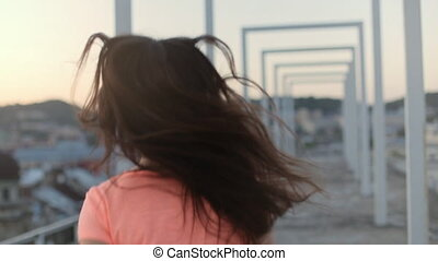 Slender girl running and turning on top of building with modern arches, city landscape background. Hair fluttering in the wind