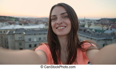 Close-up of charming tourist holding a video camera and taking selfies at sunset view from top of building, enjoying evening cityscape