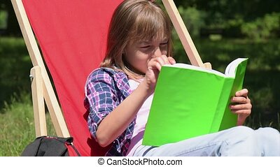 Girl reading book - Beautiful little girl reading book at...