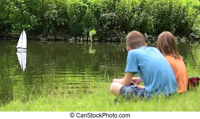 Children with remote controlled boat - Girl and boy playing...