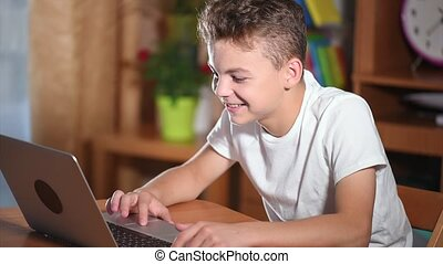 Teen boy working on laptop - Happy young boy using laptop...